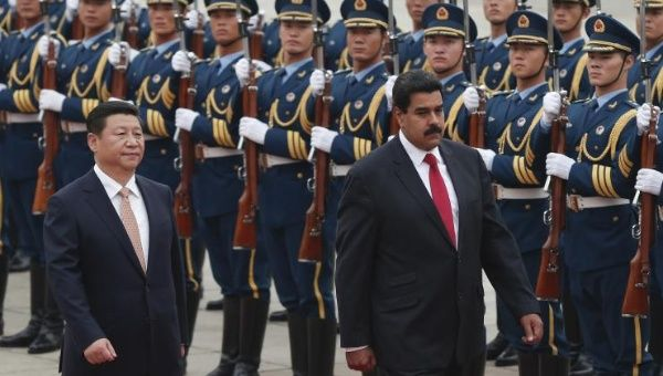 Chinese President Xi Jinping inspects an honour guard with Venezuelan President Nicolas Maduro (R) at a welcoming ceremony outside the Great Hall of the People in Beijing