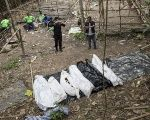 Policemen monitor as forensic experts dig out human remains near an abandoned human trafficking camp in the jungle at Bukit Wang Burma in Malaysia on May 26, 2015.