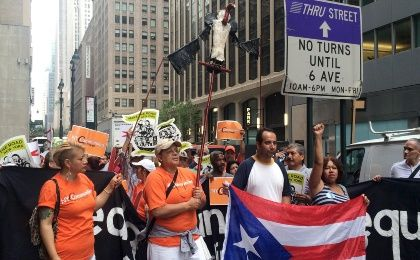 Protesters carry a vulture puppet and chant in Spanish outside the Park Avenue offices of a major holder of Puerto Rico