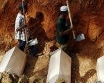 Workmen walk among coffins in a mass grave of unidentified Rohingya remains found at a traffickers camp in Malaysia.