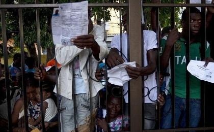 Haitians show their papers while clinging to the fence surrounding the Ministry of Interior and Police.