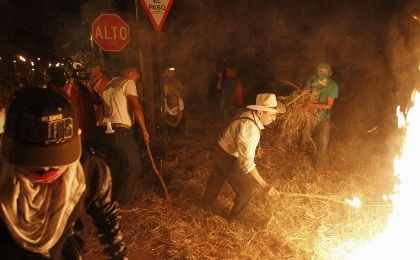 A demonstrator sets fire to hay during a march to demand the resignation of Honduras