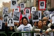 Demonstrators holding posters with the portraits of missing or killed relatives protest in Santiago, Chile.