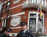 Police officers stand outside the Ecuadorean embassy in London August 13, 2015.