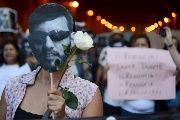 Demonstrators hold flowers, candles and sign during a demonstration against the murder of photojournalist Ruben Espinosa.