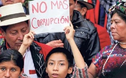 "Indigenous protesters carry a sign that reads ""No more corruption."""