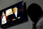 A man watches Guatemala's President Otto Perez's speech at the Presidential House in Guatemala City, Guatemala Aug. 23, 2015.