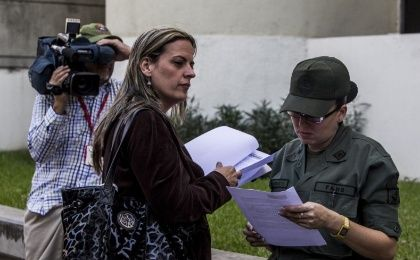 Members of the Committee of Guarimba Victims Yendri Velazquez (R) and Desiree Cabrera declare outrage over international plot revelations at the Colombian Embassy in Caracas.