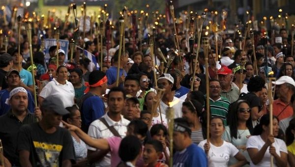 Thousands of Hondurans join anti-corruption torch-lit marches.