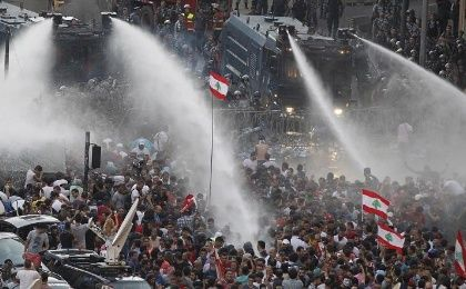 Lebanese protesters are sprayed with water during a protest against corruption and against the government's failure to resolve a crisis over garbage disposal, near the government palace in Beirut on August 23, 2015.