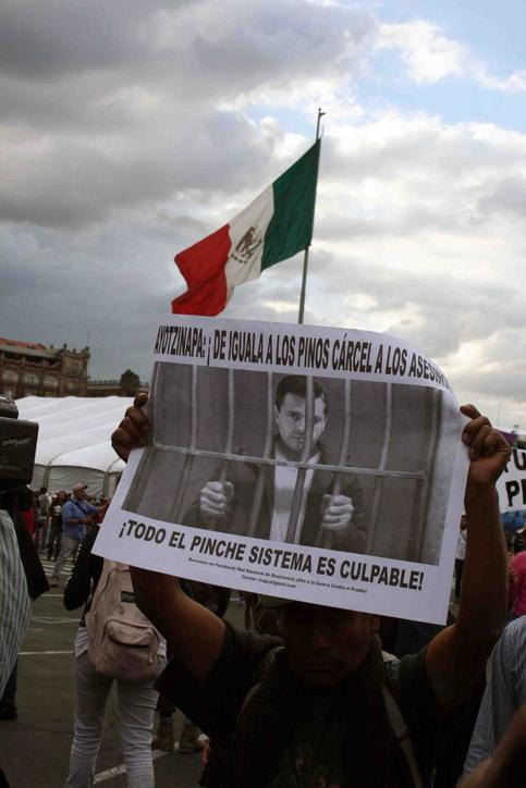 "A man holds an image of President Enrique Peña Nieto behind bars, it reads ""The whole damn system is guilty."""