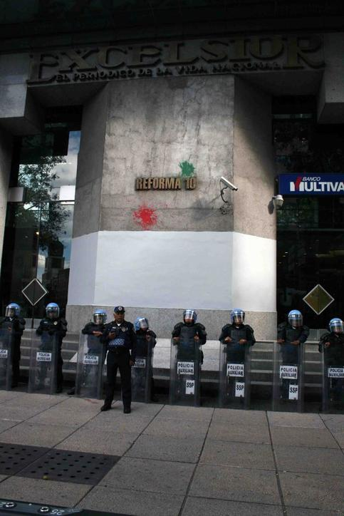 Police stand guard at demonstrations to mark the 11-month anniversary of the Ayotzinapa students