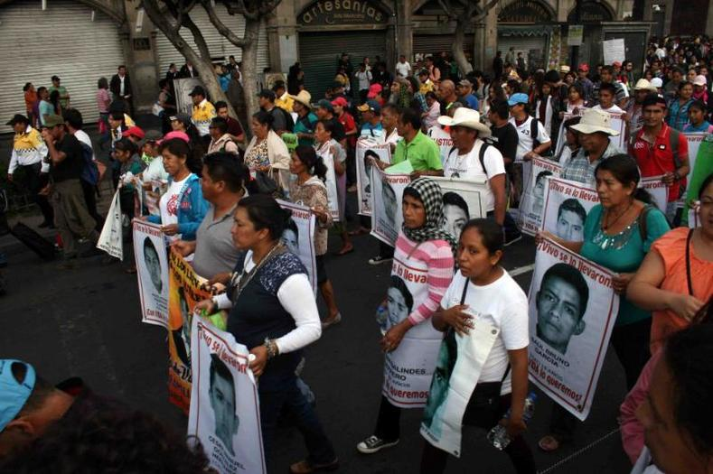 Relatives carry photos of some of the 43 missing students of the Ayotzinapa teachers
