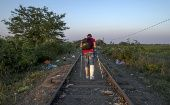A refugee, hoping to cross into Hungary, walks along a railway track near the village of Horgos in Serbia, towards the border it shares with Hungary, September 1, 2015.