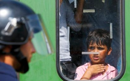 A refugee boy looks at a Hungarian policeman at the railway station in the town of Bicske, Hungary, September 3, 2015. A camp for refugees and asylum seekers is located in Bicske.