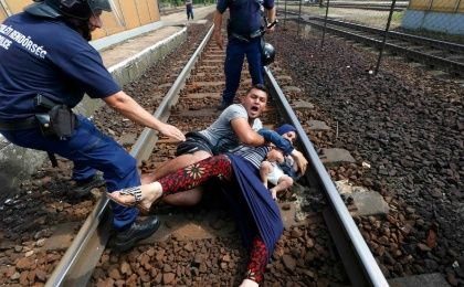 Hungarian policemen stand by the family of refugees as they wanted to run away at the railway station in the town of Bicske, Hungary, September 3, 2015.