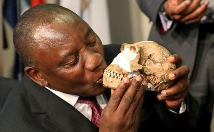 South Africa's Deputy President Cyril Ramaphosa kisses a replica of the skull of a newly discovered ancient species, named