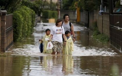 A family wades through a residential area flooded by the Kinugawa river, caused by typhoon Etau, in Joso, Ibaraki prefecture, Japan, Sept. 10, 2015. One person was missing on Thursday as 90,000 people were ordered to evacuate after rivers burst their banks in cities north of Tokyo following days of heavy rain pummeling Japan, according to local media.