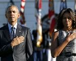 U.S. President Barack Obama and first lady Michelle Obama observe a moment of silence on the South Lawn of the White House to mark the 14th anniversary of the 9/11 attacks.