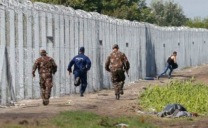 Officers chase a migrant who crossed into Hungary on Saturday
