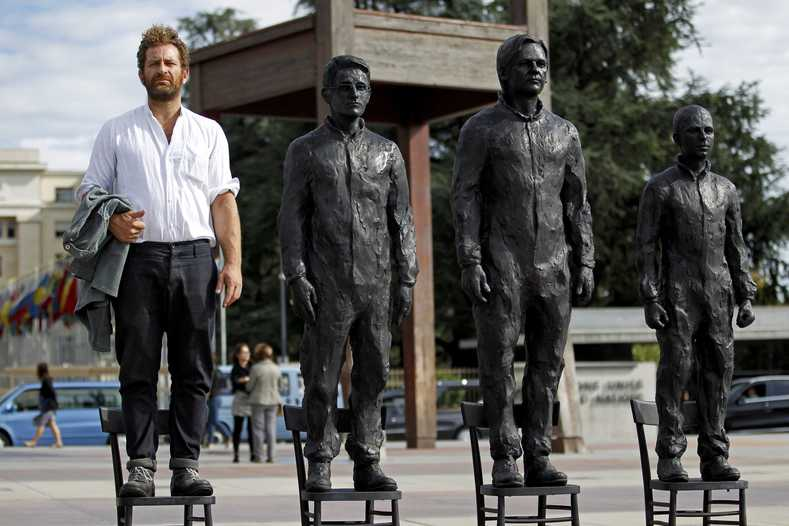 "Italian artist Davide Dormino takes part in his installation ""Anything to Say?"", a bronze sculpture representing whistleblowers Edward Snowden, Julian Assange and Chelsea Manning on the Place des Nations in front of the United Nations European headquarters in Geneva, Switzerland Sept. 14, 2015."