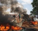 An anti-coup protester stands near a burning barricade in Ouagadougou, Burkina Faso, September 19. Burkina Faso has been in a state of crisis for days, amid a military coup.