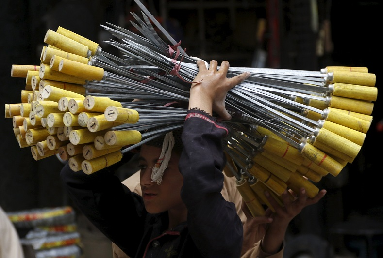A boy carries skewers to be sold as the Eid holiday begins in Peshawar, Pakistan.