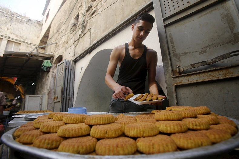 A Palestinian vendor sells traditional cookies ahead of the Eid al-Adha festival, in the West Bank city of Nablus.