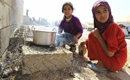 Two Syrian refugee girls cook in a refugee camp near the border with Jordan