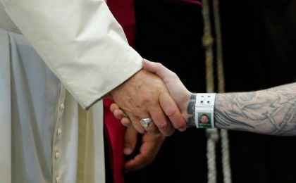 Pope Francis shakes hands with an inmate as he meets with prisoners at Curran-Fromhold Correctional Facility in Philadelphia, September 27, 2015.