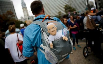 A man carries a toy version of Pope Francis, Philadelphia, Sept. 27, 2015.