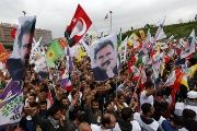 Supporters of the Pro-Kurdish Peoples' Democratic Party (HDP) wave flags with a picture of the jailed Kurdish leader Abdullah Ocalan and flags with a picture of Turkey's founder Ataturk during a n election rally.