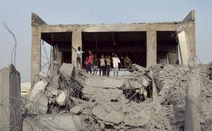 Boys stand on the rubble of a sports union building destroyed by Saudi-led airstrikes in Yemen
