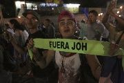 A demonstrator gestures as she holds a headband reading 'Juan Orlando Hernandez out' during a march to demand the resignation of Honduras' President Hernandez in Tegucigalpa, September 11, 2015. The protesters are calling for the resignation of Hernandez over a $200-million corruption scandal at the Honduran Institute of Social Security.
