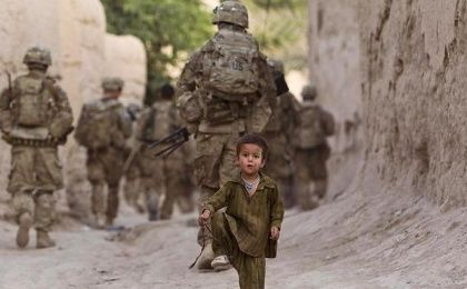 A boy plays on a street as U.S. Army soldiers of the Battle company patrol during a mission in Zahri district of Kandahar province, southern Afghanistan May 30, 2012.
