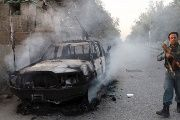 An Afghan policeman patrols next to a burning vehicle in the city of Kunduz after U.S. tragic bombing of hospital.