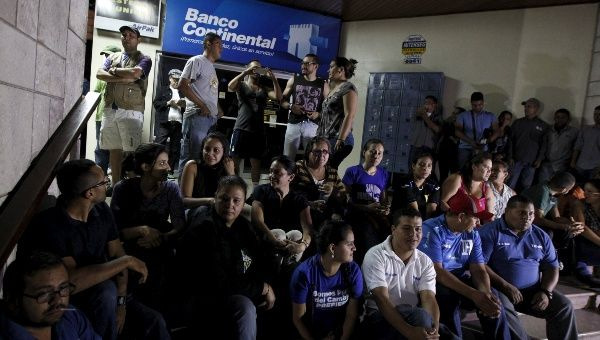 Banco Continental employees gather outside a branch of the bank in Tegucigalpa after the government ordered its liquidation, Oct. 11, 2015.