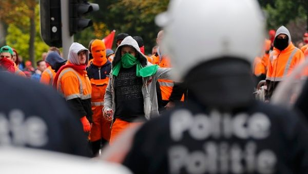 Demonstrators confront riot police in central Brussels during a protest over the government