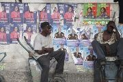 Men sit on wheelbarrows next to posters of candidates running for elections along a street in Port-au-Prince, Haiti, Oct. 20, 2015. Haiti will hold elections on Oct. 25.