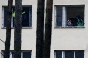Refugees stare out of the window of a Czech migrant detention center.