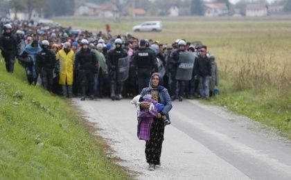Police officers escort Fatima from Syria (front) and other migrants as they make their way on foot after crossing the Croatian-Slovenian border.
