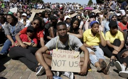 Students sit in protest during a mass demonstration on the steps of Jameson Hall at the University of Cape Town, October 22, 2015.
