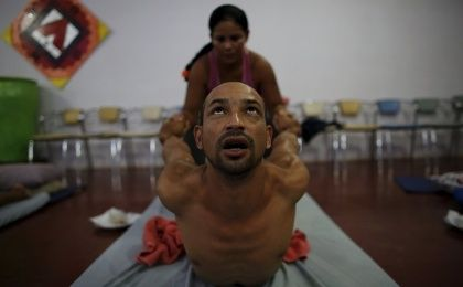 An occupational therapist (back) conducts an Ayurvedic massage on prisoner Anderson Miranda, 33, as part of the ACUDA program, at a complex of ten prisons in Porto Velho, Rondonia State, Brazil, Aug. 27, 2015. Ayurveda is an ancient Hindu system of holistic healing. The massage is taught to the prisoners to help them understand the human body and engender a greater sense of compassion for others, according to ACUDA.