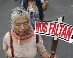 A demonstrator holds a sign as she takes part in a march in Mexico City to mark the one-year anniversary of the disappearance of 43 students.