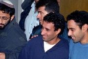 Yigal Amir (R), Yitzhak Rabin's confessed assasin, smiles as he greets his brother Hagai Amir (c), during a Tel Aviv court hearing in 1995.