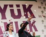 Figen Yüksekdağ and Selahattin Demirtaş address a crowd of supporters with a huge banner behind them saying