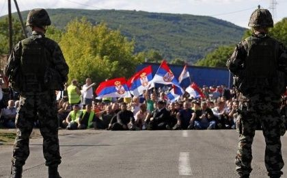 Kosovo Serbs wave flags while sitting on the road in front of Slovenia