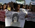 School students hold signs during a demonstration against the violation of women's rights and to mark International Women's Day, at Copacabana beach in Rio de Janeiro The sign at center reads:
