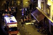 General view of the scene with rescue service personnel working near covered bodies outside a restaurant following shooting incidents in Paris, France, November 13, 2015.