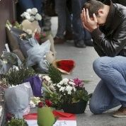 A man pays his respect outside the Le Carillon restaurant the morning after a series of deadly attacks in Paris Nov. 14, 2015.